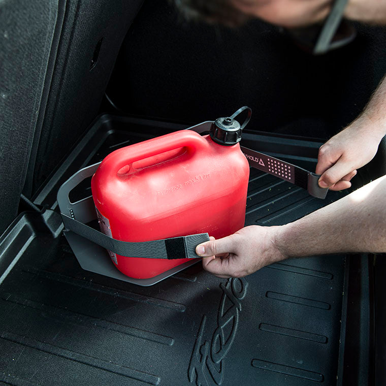a man fastening Stayhold elasticated combi-straps around a fuel can to hold it securely in the car boot