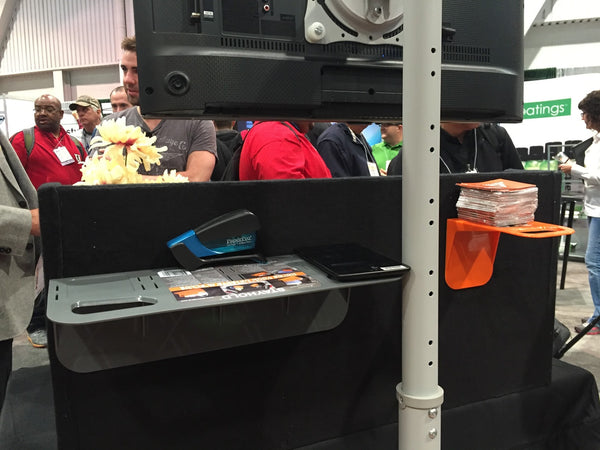 Using STAYHOLD™ Cargo Organiser as impromptu shelves at a tradeshow