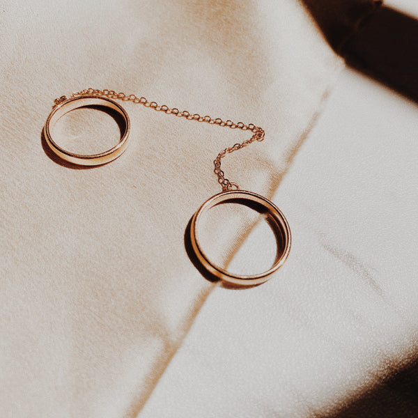 Two rose gold rings connected by a chain and can be worn on two different fingers or the same one.