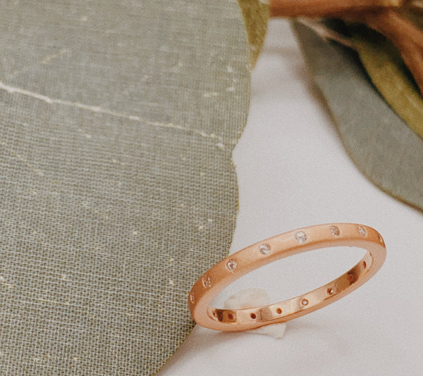 Matte rose gold ring with 18-eternity stones.