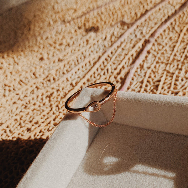 Rose gold ring with bezeled pear-shaped gem with dangled chain.