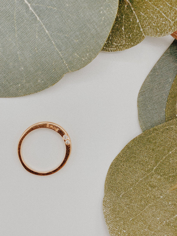 Rose gold ring with two 2mm diamonds bezeled and 'k mae' engraved.