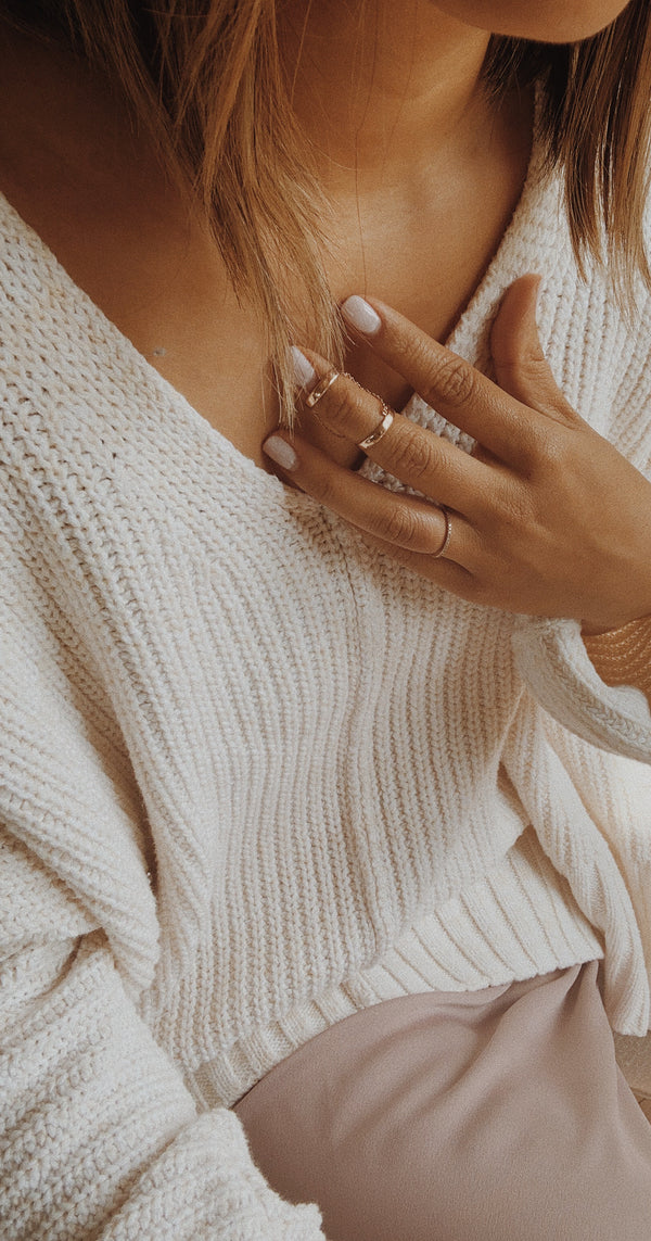 Two rose gold rings connected by a chain and meant to be worn on the same finger.