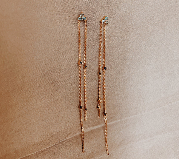 Rose gold dangle earrings with two cable chains dropped with topaz and black sapphire gems.