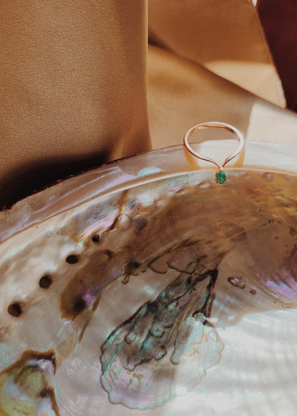 Rose gold midi ring with a pear shaped emerald gem.
