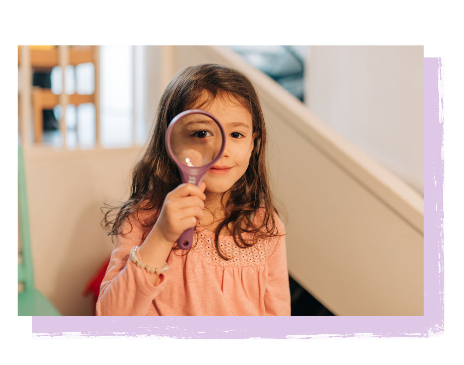 Little girl looking through magnifying glass looking hopeful.