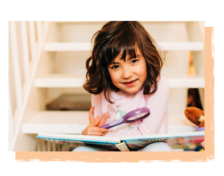 Little girl sitting on stairs with magnifier and The Adventures of Lillicorn book open by STEM educational publisher QuestFriendz