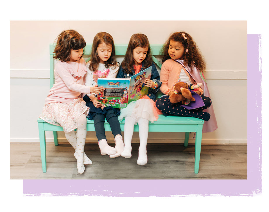 Four little girls sitting on bench with The Adventures of Lillicorn book open by STEM publisher QuestFriendz