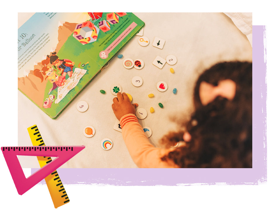 Little girl with The Adventures of Lillicorn book open on floor solving a STEM quest
