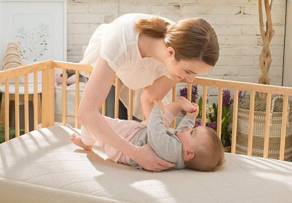 satara-home-naturepedic-organic-breathable-ultra-2-stage-chemical-free-crib-mattress-mom-with-baby-lifestyle-image