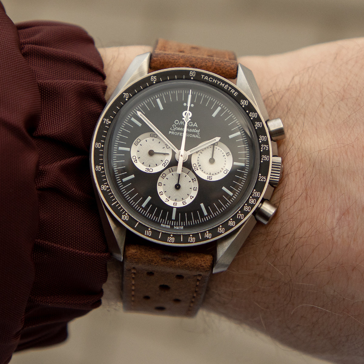 JPM Racing strap in peanut on the wrist with Omega Speedmaster