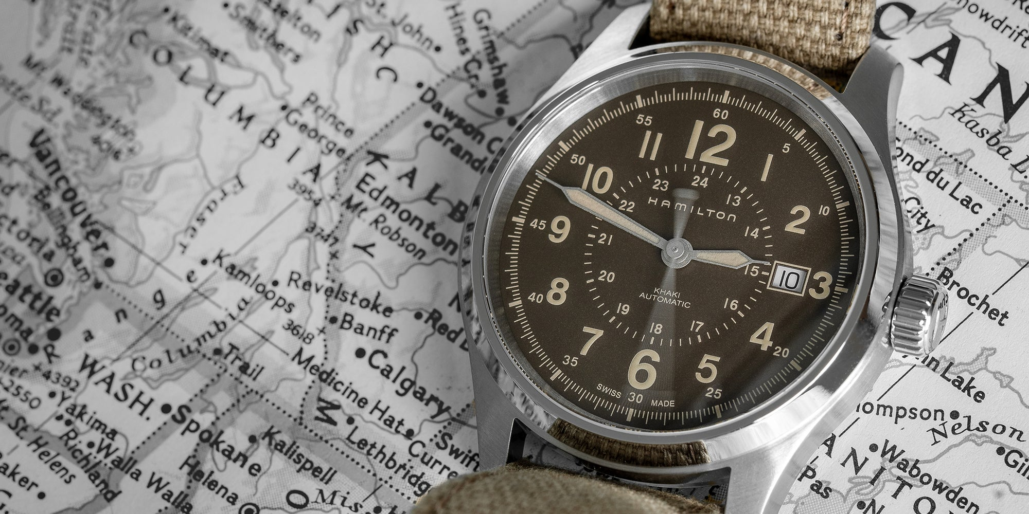 Hamilton khaki field with canvas strap laying flat on a map