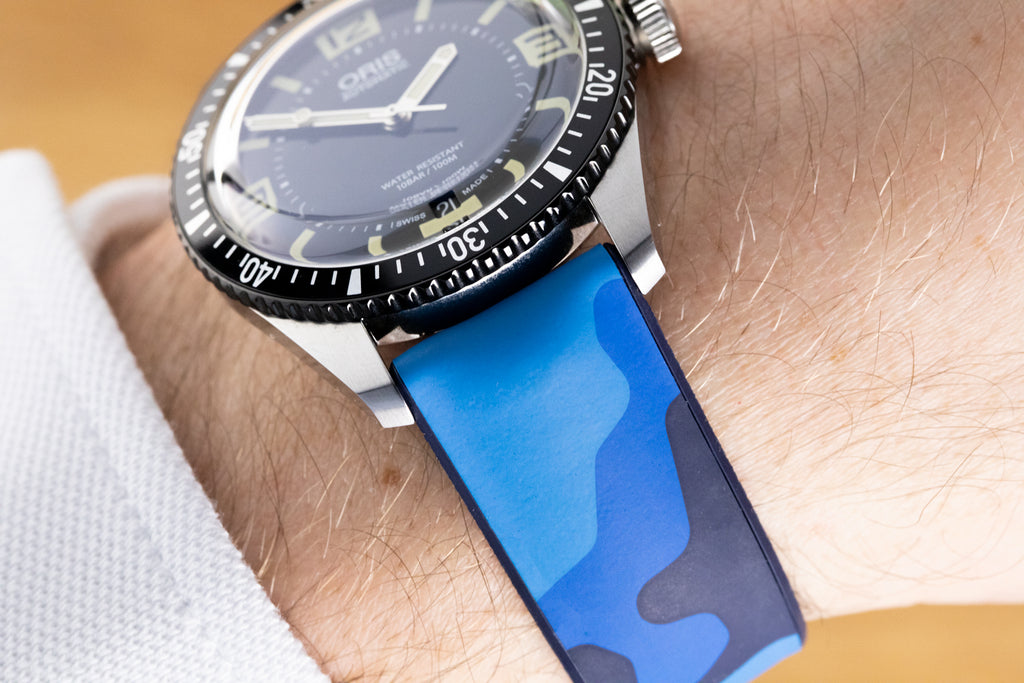 Blue camouflage watch strap and dive watch on the wrist.