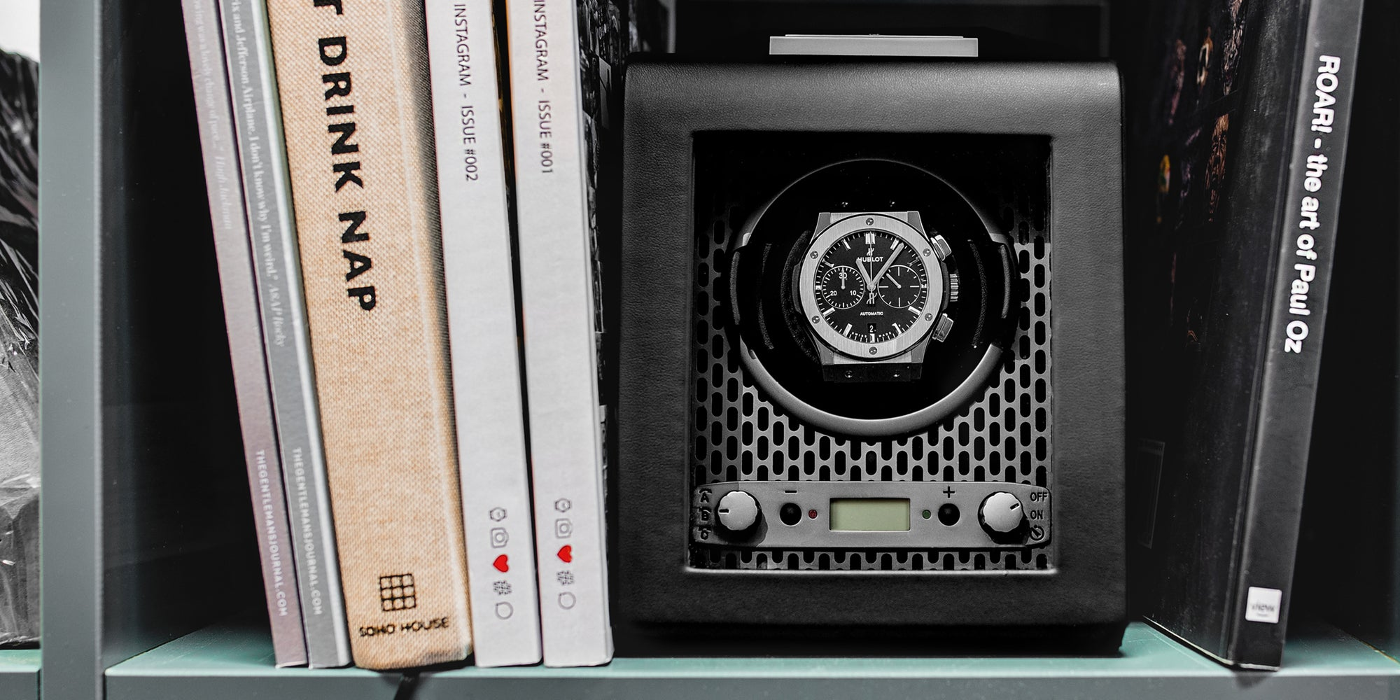 Hublot classic fusion in the WOLF Axis watch winder on a shelf with books