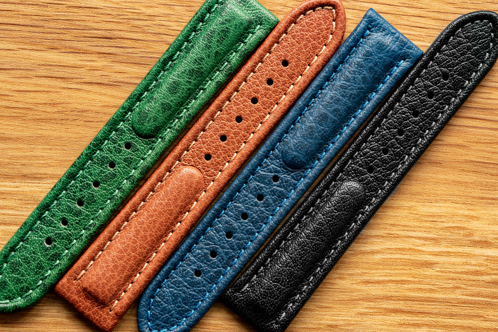 Green, gold brown, blue and black Polo Sherpa watch strap lengths lined up on a wooden desk.