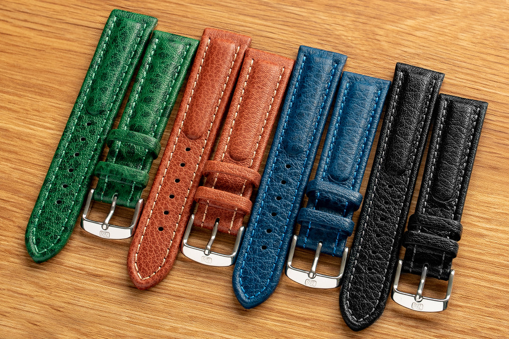 Row of Di-Modell watch straps in different colours on a desk. Green, brown, blue and black is how they line up.