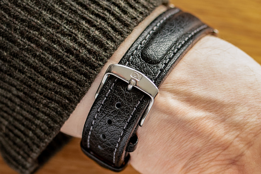 Fastened black watch strap and silver buckle being worn with a knitted jumper.
