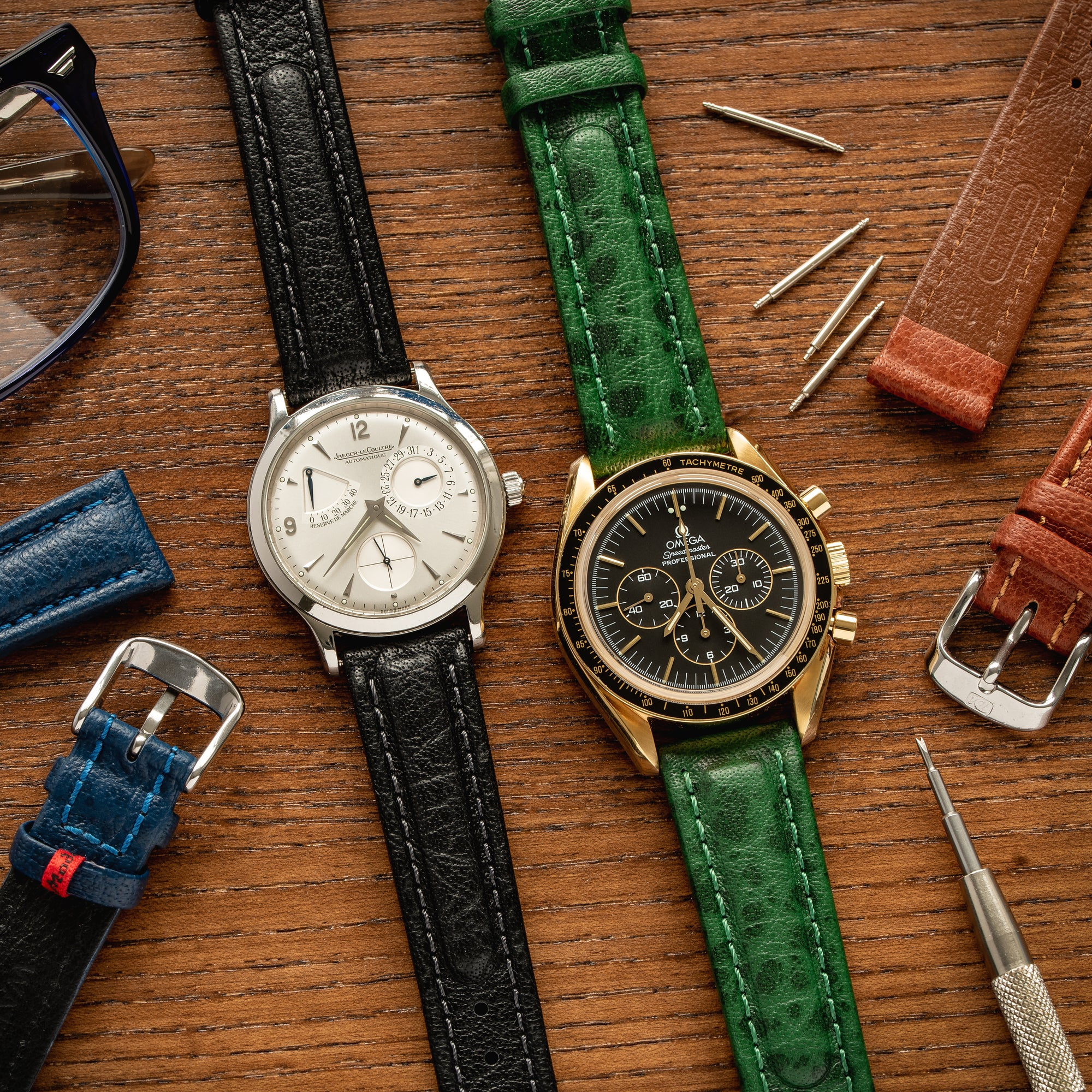 JLC and Omega watches lay flat on a table with selection of Di-Modell Polo Sherpa straps
