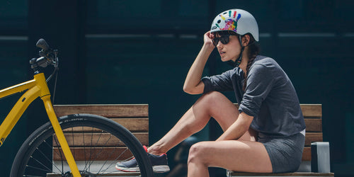 woman riding bike with Melon Urban Active Rainbow Red bicycle helmet