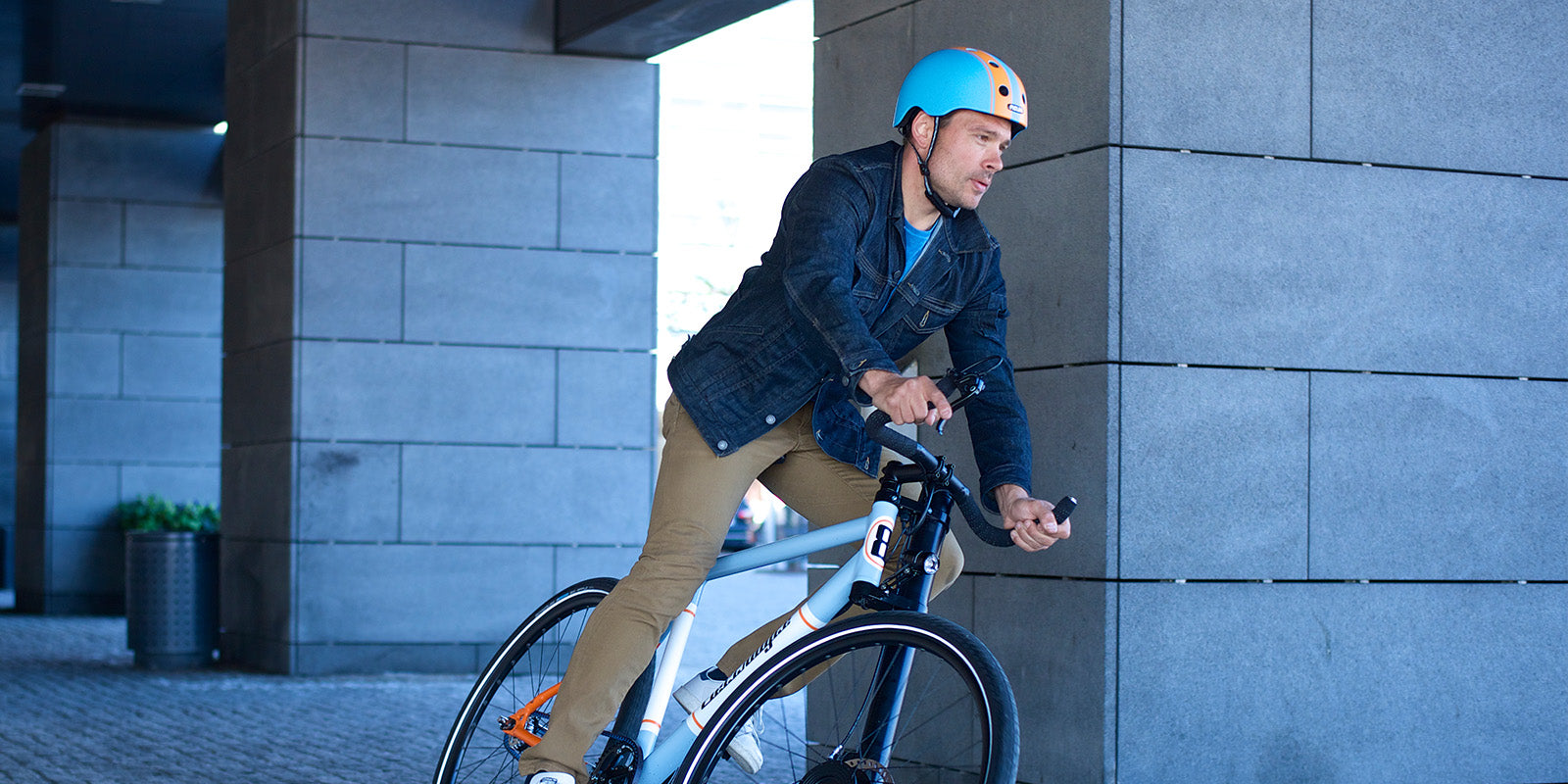 Man riding bicycle with Melon Urban Active Double Orange Blue Bicycle double striped bicycle helmet