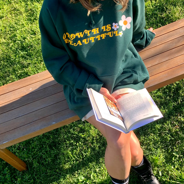 Girl reading compound effect book on a vintage park bench wearing an oversized green hoodie with growth is beautiful quote and flower prints