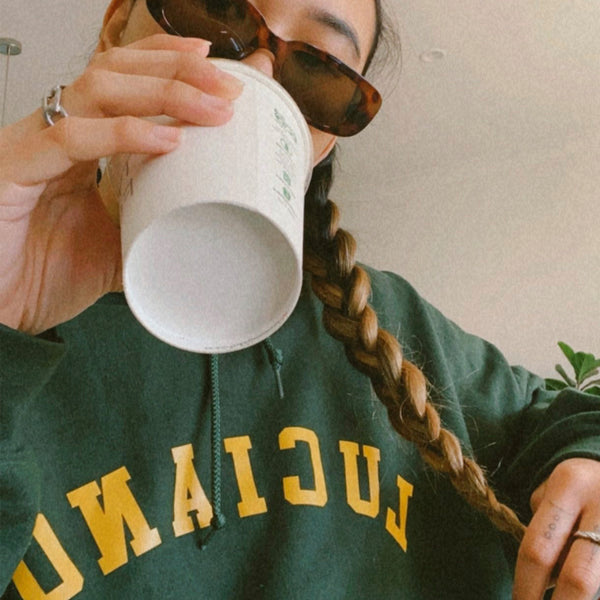 Girl in braids wearing an oversized green hoodie drinking coffee with vintage sunnies and plant at the back