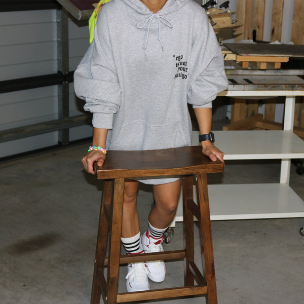 oversized sports grey hoodie with ego is not your amigo girl wearing air jordan 2 posing with wooden vintage stool