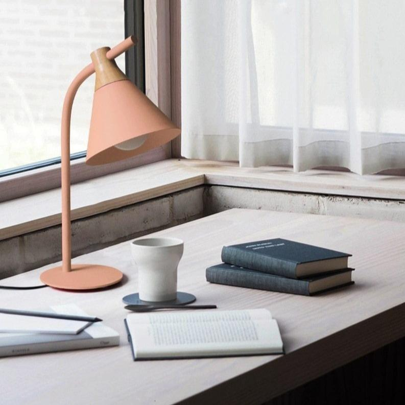 pink-desk-lamp-on-a-table-with-books-and-a-mug-Zavato-Home
