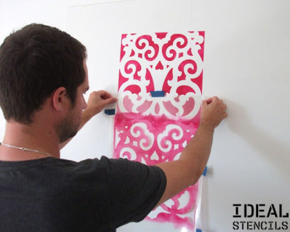 positioning a Moroccan style stencil on wall before painting
