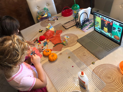 Two kids participating in a live online craft activity