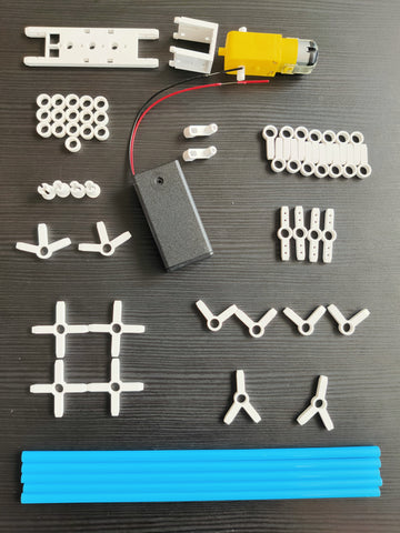 layout of blue straw, white plastic connectors, AA battery case and DC motor on a black table background