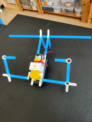 modified blue straw robot with white connectors and dc motor on black wooden table