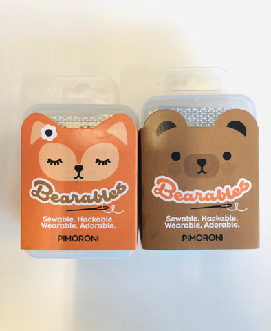 Cute orange cartoon fox and adorable brown bear packaging on plastic box against a white background