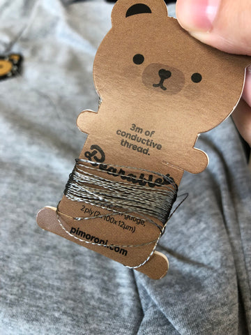 conductive thread coiled around a cute brown bear spool on a grey shirt background