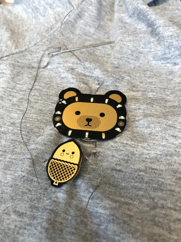 assembled electronic bear badge and acorn sensor with conductive thread on grey shirt