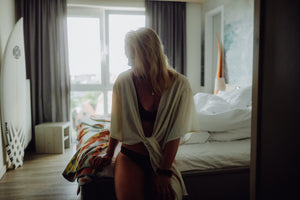 Blonde girl sitting on bed in hotel room wearing WOODSTRK bikini in merlot red & a white cardigan