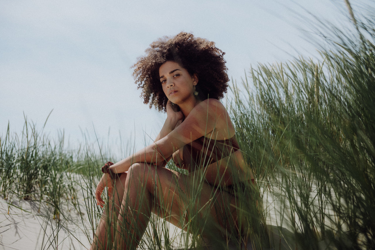 Girl with afro sitting in the dunes wearing WOODSTRK bikini in merlot red
