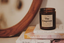 Load image into Gallery viewer, Shy Wolf The Empress candle resting on a stack of books.