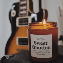 Load image into Gallery viewer, Shy Wolf Sweet Emotion candle with a guitar in the background.