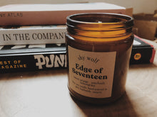 Load image into Gallery viewer, Shy Wolf Edge of Seventeen candle on a live edge wood nightstand with books.