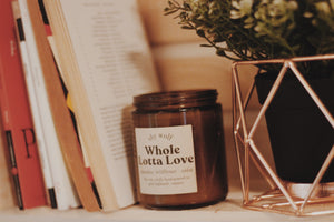 Whole Lotta Love candle by Shy Wolf Candles resting on a bookshelf.