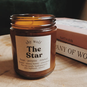 The Star candle by Shy Wolf Candles sitting on a live edge wood nightstand in front of books.