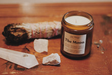 Load image into Gallery viewer, The Moon by Shy Wolf candles on warn wood table with sage, and crystals.