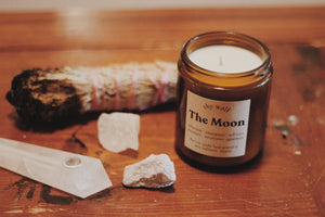 The Moon by Shy Wolf candles on warn wood table with sage, and crystals.
