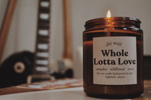 Load image into Gallery viewer, Close up photo of a Whole Lotta Love candle burning with a guitar in the background.