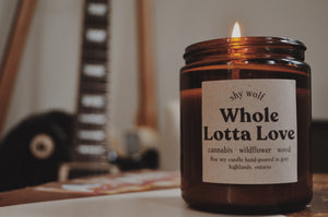 Close up photo of a Whole Lotta Love candle burning with a guitar in the background.