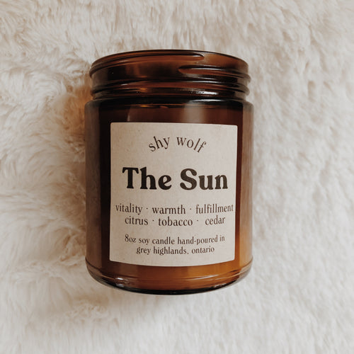 Shy Wolf The Sun candle with citrus, tobacco, and cedar.