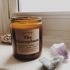 The Hierophant by Shy Wolf Candles resting on a window ledge.