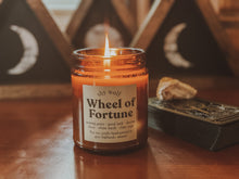 Load image into Gallery viewer, Wheel of Fortune candle burning beside a stack of tarot cards.