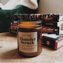 Load image into Gallery viewer, Thunder Struck candle by Shy Wolf Candles sitting on a live edge coffee table in front of books.